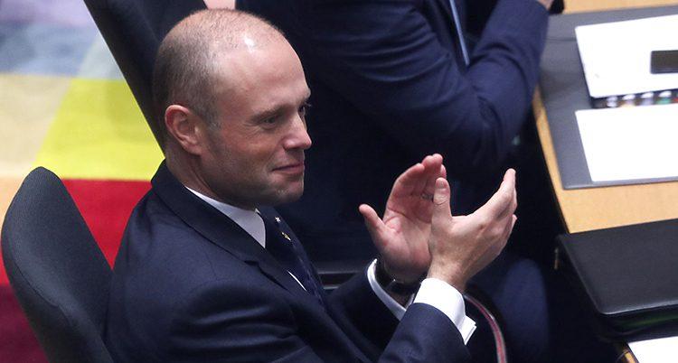 Maltas ledare Joseph Muscat sitter på ett möte i EU. Han applåderar med händerna. Han har rakat huvud och kostym.