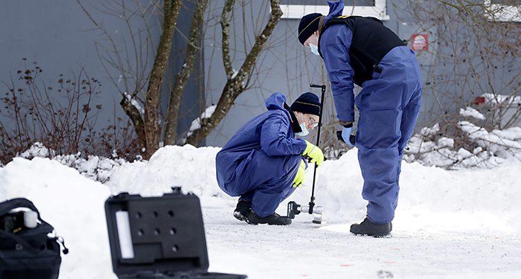 Bilden är tagen utomhus i ett bostadsområde i Sundsvall. Det är snö på marken. Två tekniker från polisen arbetar med att hitta spår efter ett mord.