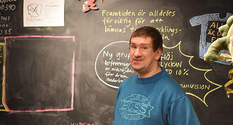 Thomas Kjellberg på sitt kontor. Bakom sig har han en svart tavla som det går att skriva på. Thomas har en turkos tröja på sig.