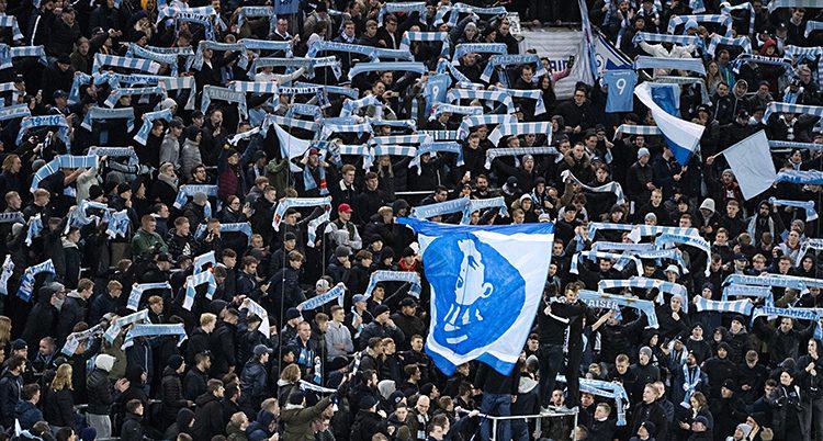 En publik med ljusblå halsdukar och flaggor