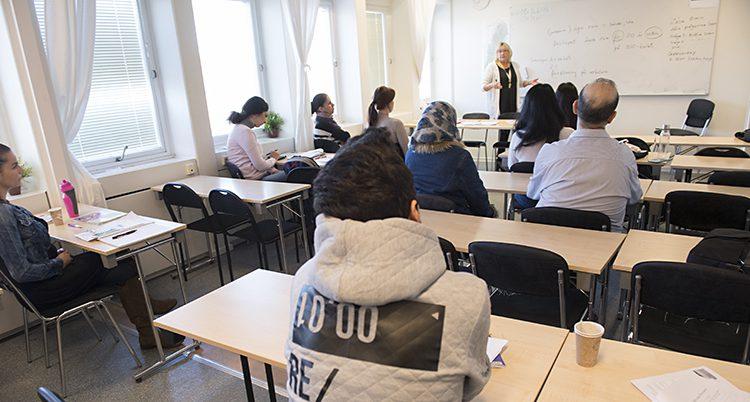 Ryggar i ett klassrum, en lärare längst fram