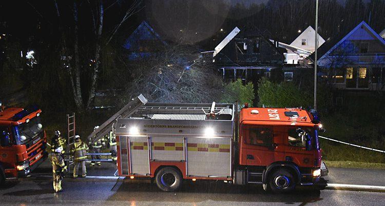 En brandbil på en mörk gata framför ett radhus