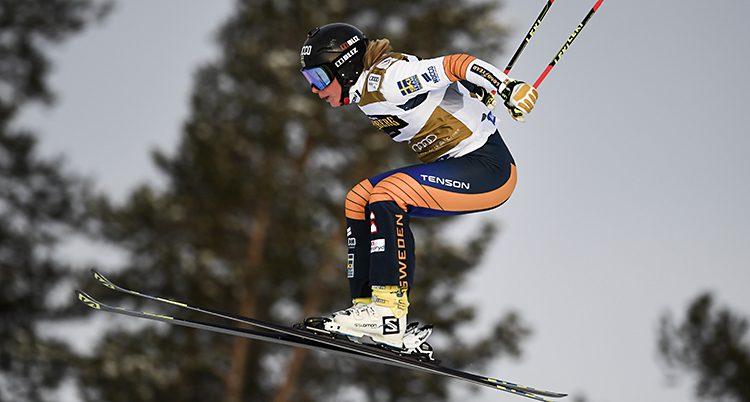 Hon hoppar i luften med korta skidor