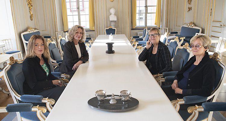 Fyra kvinnor sitten i en fin sal vid ett långt vitt bord. De ler.