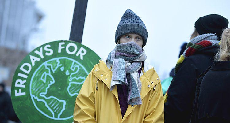 Greta i sin gula regnrock med en halsduk för mun och näsa i kylan.
