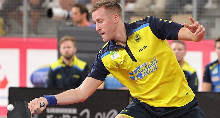 Falck i gul landslagströja under en match. Han slår bollen med sin racket.