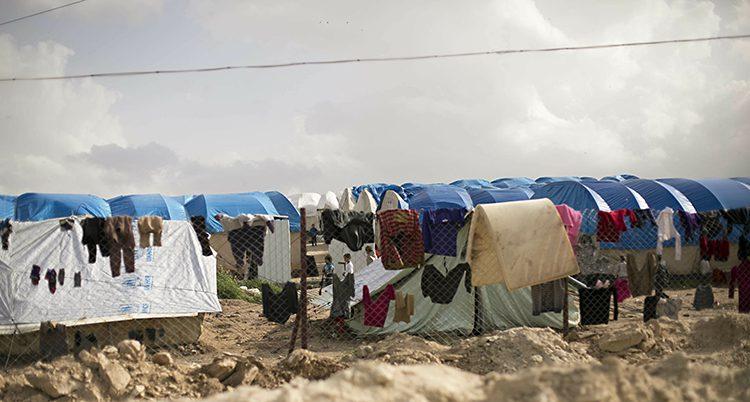 Kläder hänger på tork framför vita tält