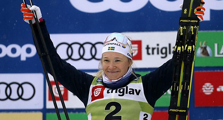 Jonna ler och lyfter armarna. Hon har skidorna i ena handen och stavarna i den andra.