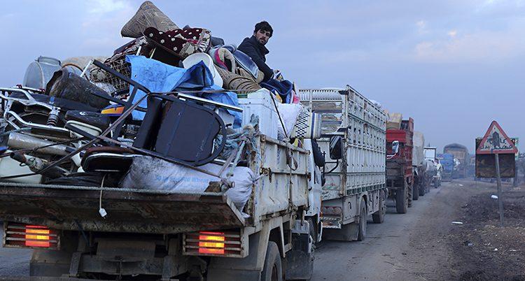 Människor sitter på lastbilar fulla med möbler.