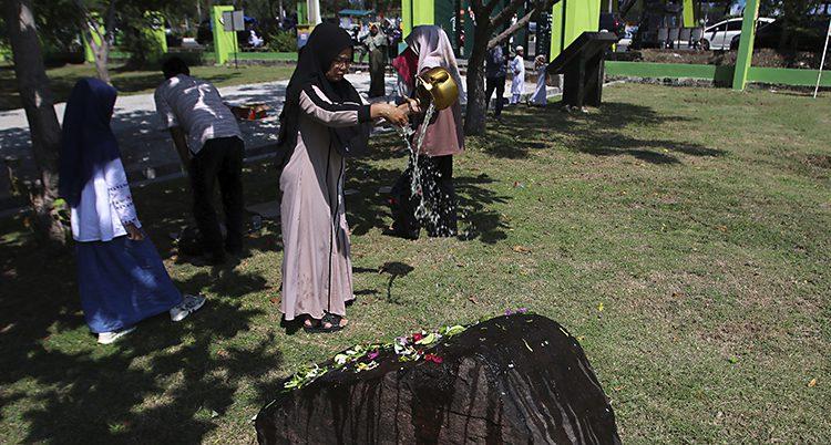 Kvinnor i slöja har samlats. De har lagt blommor på en svart sten