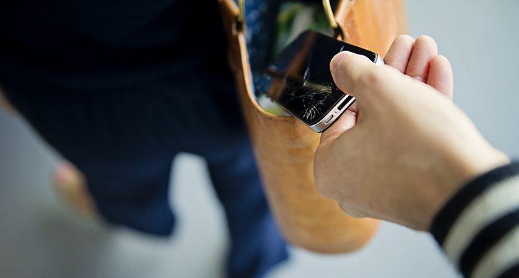 En hand tar en mobil ur en väska.