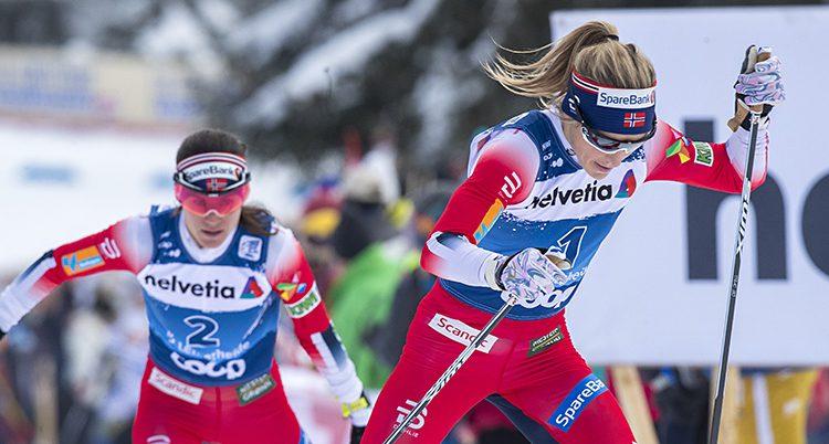 Två norska skidåkare kämpar i en backe.