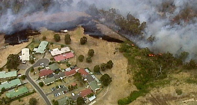 En bild som är tagen från ett flygplan. Nedanför syns flera hus. Nära husen är det en brand i skogen. Det kommer mycket rök.