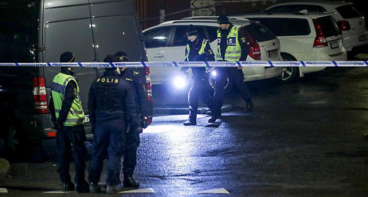 Bilden är tagen utomhus. Det är mörkt. Man ser flera poliser och flera polisbilar. Två poliser går och lyser med ficklampor.