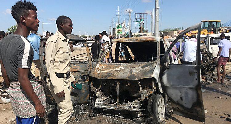 Människor står och tittar på resterna av en bil. En har uniform. Bilen är helt förstörd.