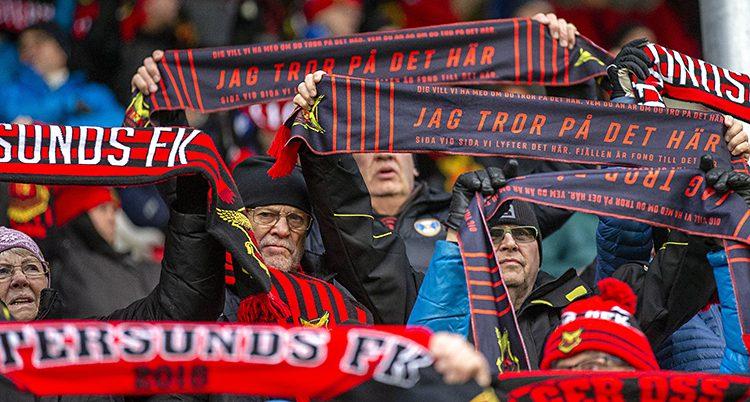 Människor på en läktare . De håller upp halsdukar där det står Östersund.