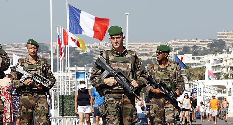 Tre soldater med vapen går efter gatan. I bakgrunden syns flaggor på halv stång.