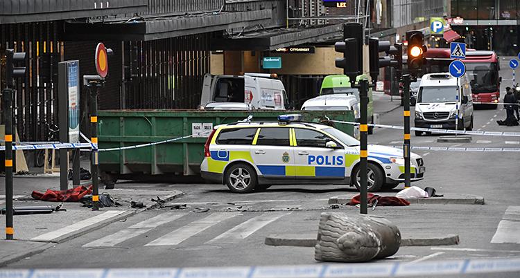 En polisbil står på gatan. Ett lejon av betong är vält-