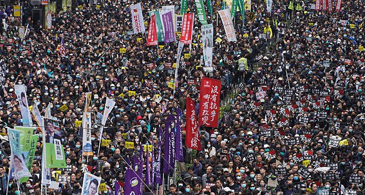 Tusentals människor står tätt tillsammans på en gata. Bilden är tagen ovanifrån.