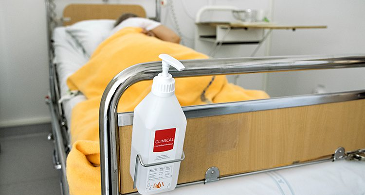 En person ligger i en sjukhussäng.