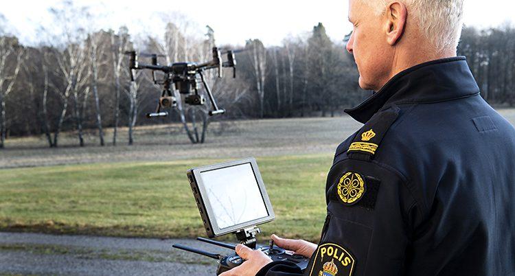 En polis i mörk uniform håller en kontroll i handen och står vänd med ryggen mot kameran. Han tittar på en drönare som är i luften framför. Det är utomhus och en skog syns bakom.