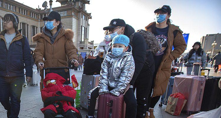 Bilden visar några personer vid en tågstation i Peking i Kina. Personerna har masker för näsa och mun.