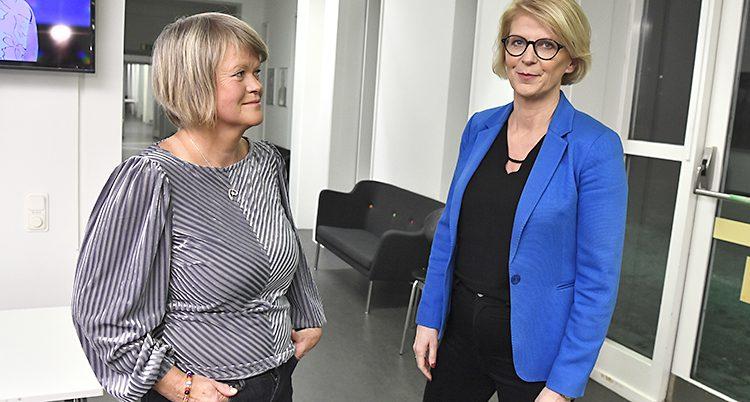 Två kvinnor står bredvid varandra och ser ganska nöjda.