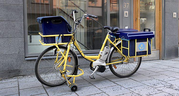 En cykel från Postnord står parkerad på en trottoar.