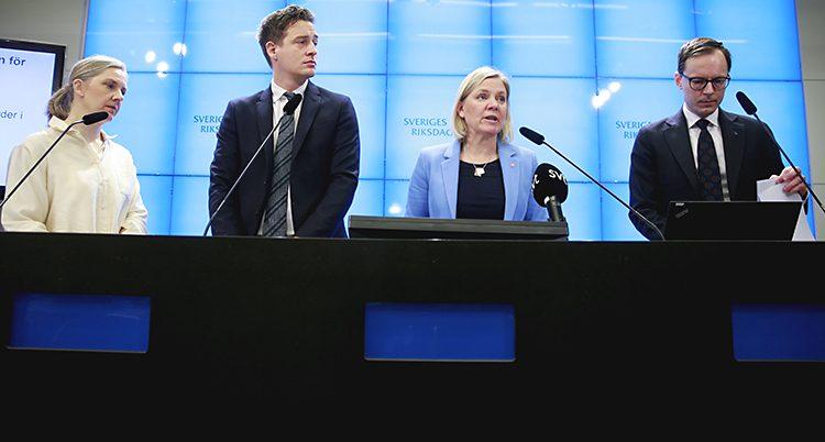 De fyra politikerna står bakom en bord vid varsin mikrofon.