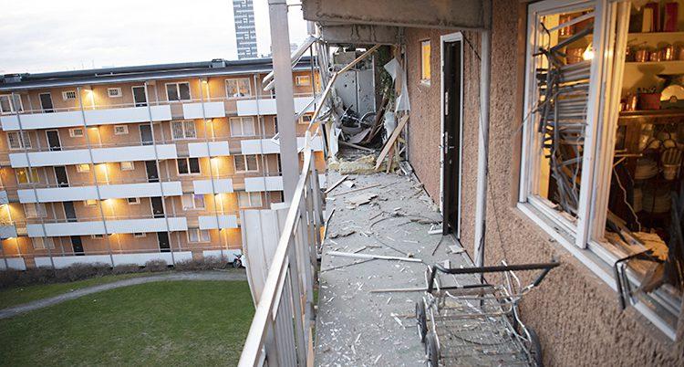 En loftgång med dörrar på höger sida. Det ligger bråte och trasiga saker på marken.