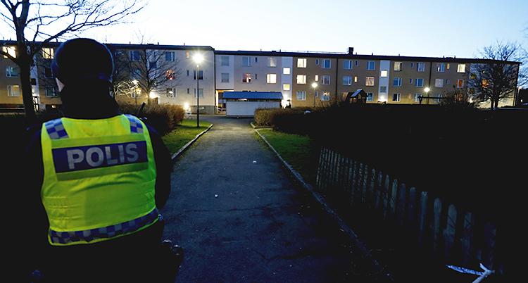 En polis står med ryggen till. Längre bort syns husen