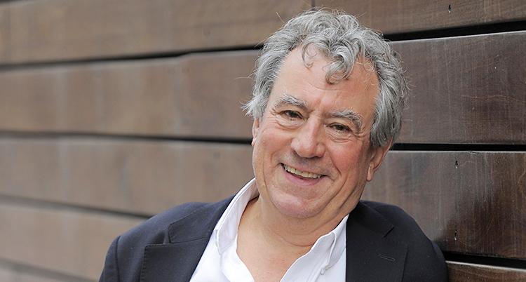 En man med grått hår som ler och ser glad ut