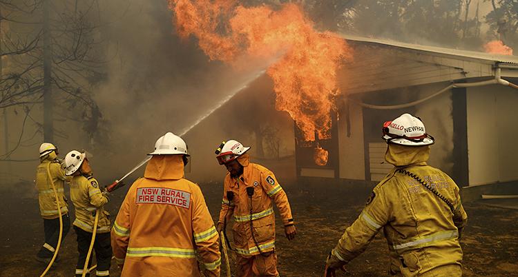 Det brinner i ett hus. Lågorna slår ut genom ett fönster. Brandmän sprutar vatten.