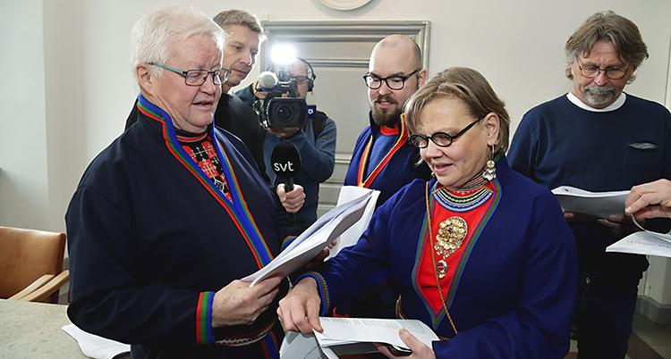 Flera personer står och läser en dom från en domstol. Några av dem har samiska dräkter på sig.