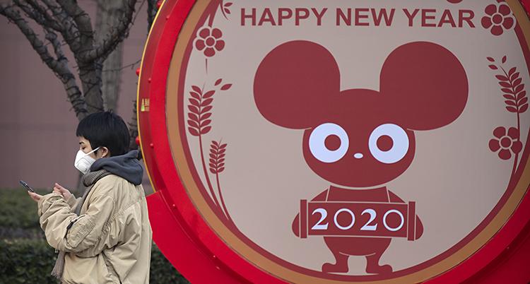 En person med munskydd går framför en skylt där det står Gott nytt år på engelska