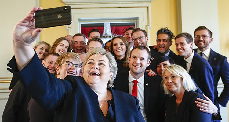 Erna håller upp en mobil och tar bild på hela den glada gruppen