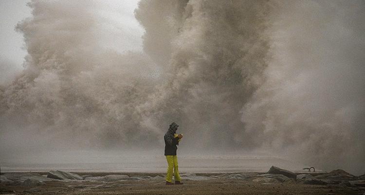 En kvinna står på en strand. En hög våg slår inen bit ut. Det ser ut som ett stort rökmoln.
