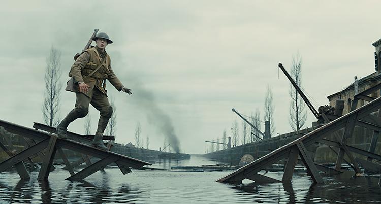 En soldat är på väg över en flod. Det är trasiga hus runt honom. Han går på resterna av en bro och ser rädd ut.