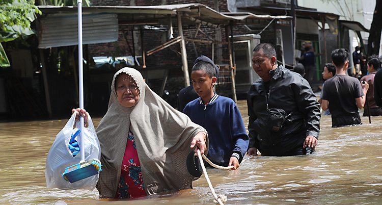 Bilden är tagen i ett samhälle nära Jakarta i Indonesien. Det är fullt med vatten på gatorna. Människor går genom vattnet som når dem upp till midjorna.
