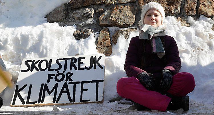 Svenska Greta Thunberg sitter på marken. Hon har vinterkläder på sig. Bakom henne syns en snödriva. Bredvid sig har hon ett plakat där det står Skolstrejk för klimatet.