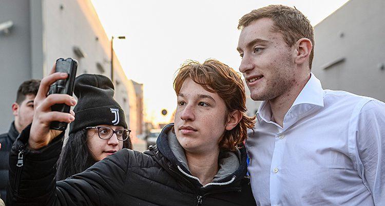Fotbollsspelaren Dejan Kulusevski har vit skjorta. Han står på en gata i staden Turin. En person står bredvid honom. Personen tar en bild på dem tillsammans med sin mobiltelefon. Bredvid står en ung kvinna med en mössa som det står Juventus på.
