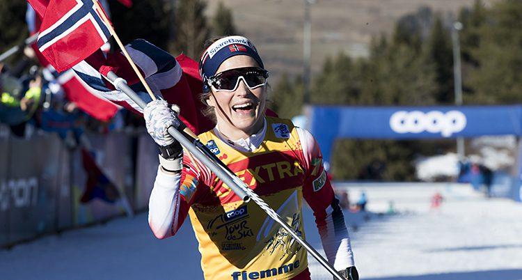 Therese har en norsk flaga i handen. Hon skrattar . Solen skiner.