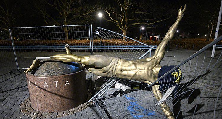 Statyn har vält. En tröja hänger över huvudet, det står Sverige på den.