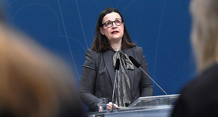 Anna Ekströmer i grått framför en mikrofon.
