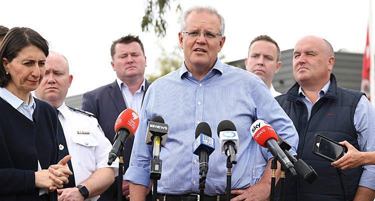 Australiens ledare Scott Morrison har en träff med journalister. Han står och pratar in i flera mikrofoner. Han har grått hår, glasögon och ljusblå skjorta. Runt honom står flera människor.