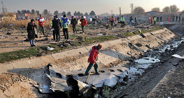 Bilden visar en öppen plats, utomhus. På marken ligger en skadad del av ett flygplan. Räddningsarbetare och andra människor går runt på platsen.
