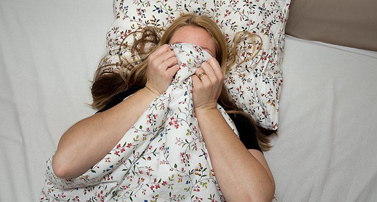 En kvinna ligger vaken i en säng. Hon har dragit täcket över huvudet.