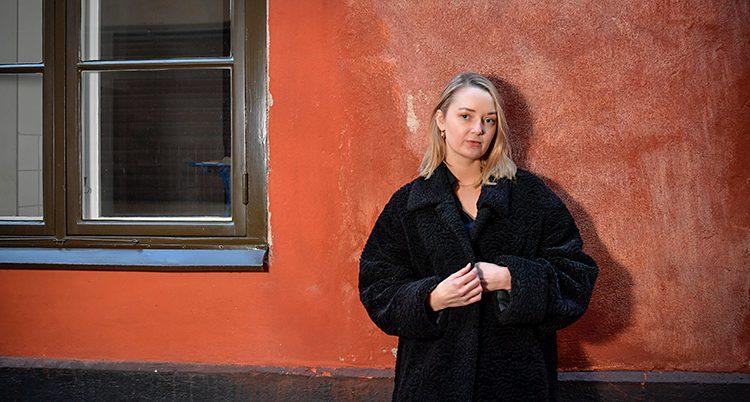 Elin Persson står mot en vägg. Den är röd. Elin har blont långt hår och en svart kappa på sig.