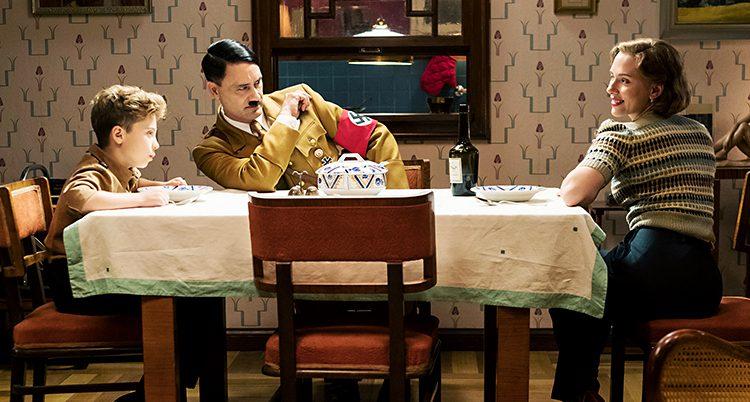 En pojke sitter vid ett bord. Mitt emot sitter en kvinna.