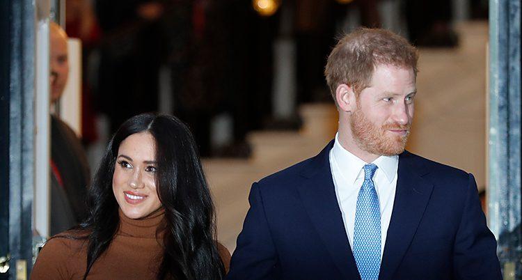 Meghan har svart hår och ler. Prinsen har rött hår, kavaj och slips